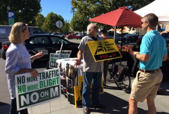 Karen Lines and Victor Valdez compete for a shopper's attention at the Menlo Park farmer's market on Oct. 11, 2014. Measure M would further restrict the amount of new office buildings that can be built downtown and on El Camino Real. (Farida Jhabvala Romero/Peninsula Press)