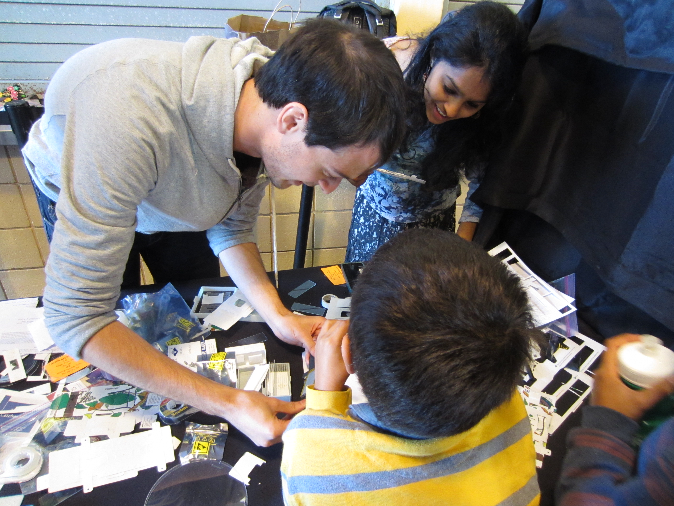 From left: William Gilpin and Sumitra Tatapudy show a young boy how to use a modified Foldscope at the table for the Prakash Lab from Stanford University. This Foldscope had a battery powered light and when Gilpin put a slide of an ant in the scope, a magnified image of the ant was projected onto the paper in front of the boy. Gilpin is a PhD student in applied physics at Stanford University, and Tatapudy is a graduate student in the Tetrad Program at University of California, San Francisco. (Shara Tonn/Peninsula Press)