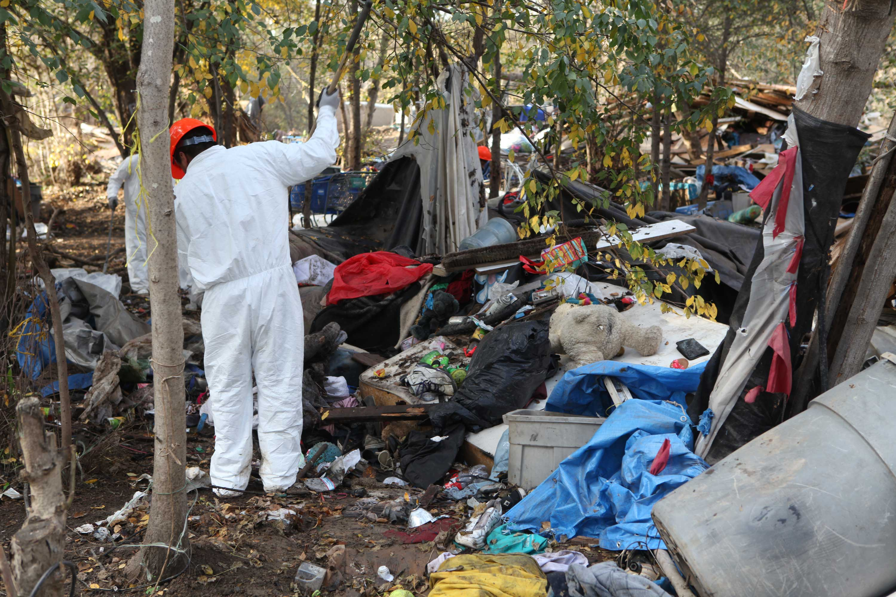 """A city worker cleans up the homeless encampment known as """"The Jungle"""" on Dec. 8, 2014, in San Jose. The City of San Jose shut down the encampment site on Dec. 4. (Yuqing Pan/Peninsula Press)"""