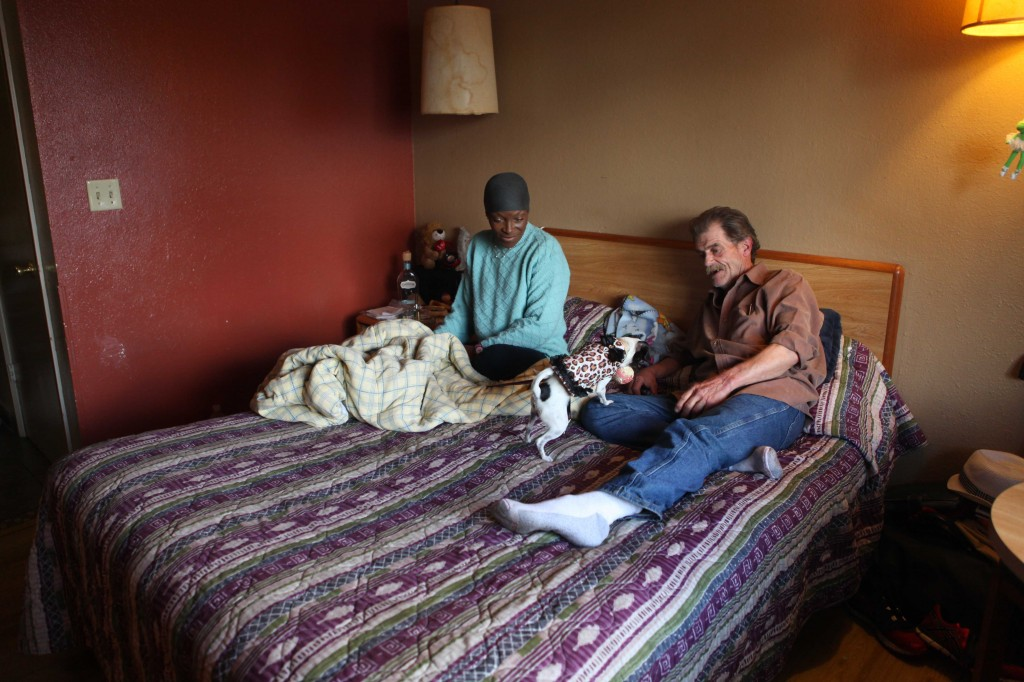 Patrick and Sandra Scott, both 62 years old, play with their dog Pepper in a motel room in Santa Clara on Dec. 13, 2014. They were placed into a motel after being homeless for almost a year. (Yuqing Pan/Peninsula Press)