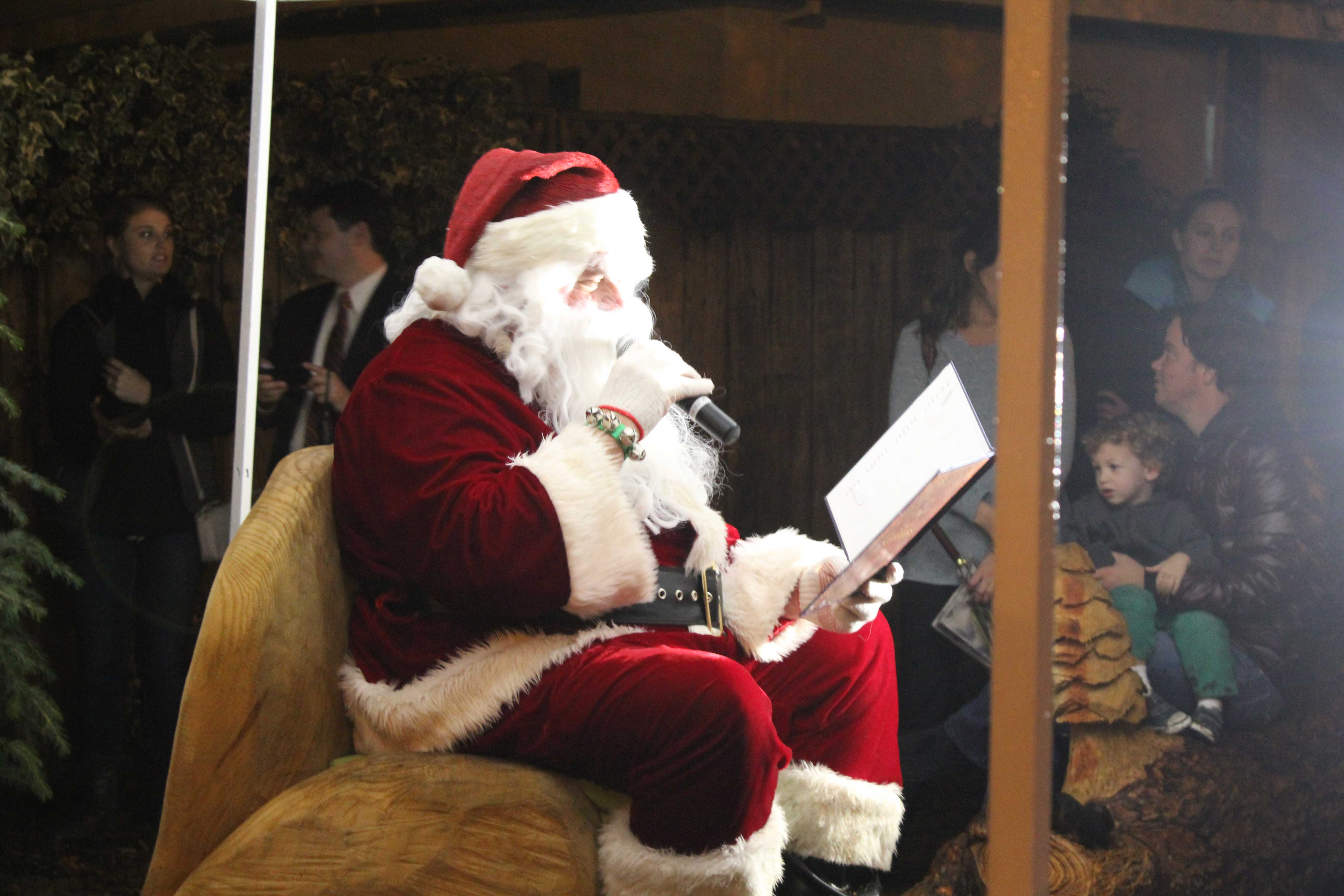 """Santa Claus reads """"The Night Before Christmas"""" to attendees of Menlo Park's second annual Christmas Tree lighting in Fremont Park. (Sabrina Elfarra/Peninsula Press)"""