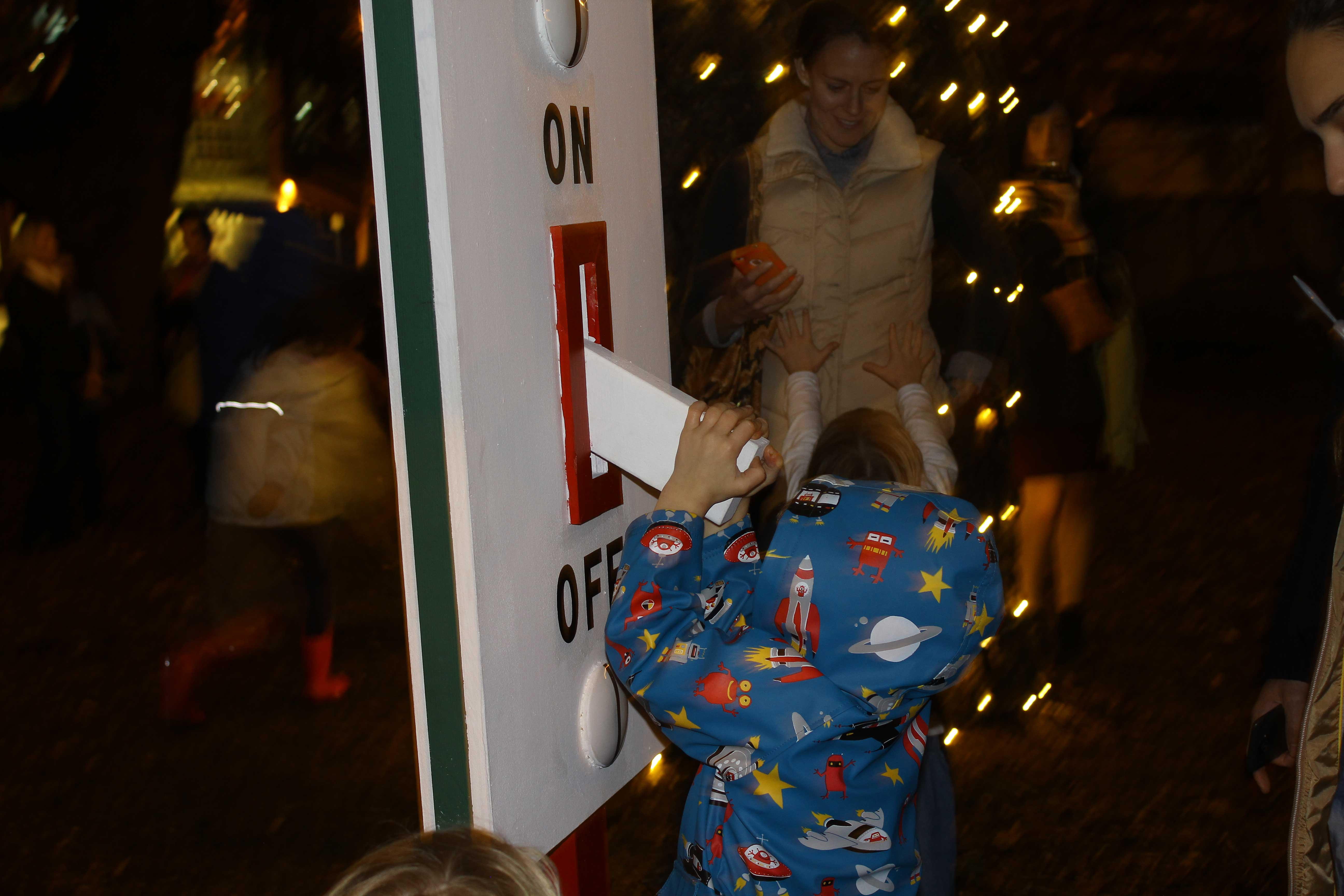 Children at the Menlo Park Christmas-Tree lighting, play with the tree switch in Fremont Park. (Sabrina Elfarra/Peninsula Press)