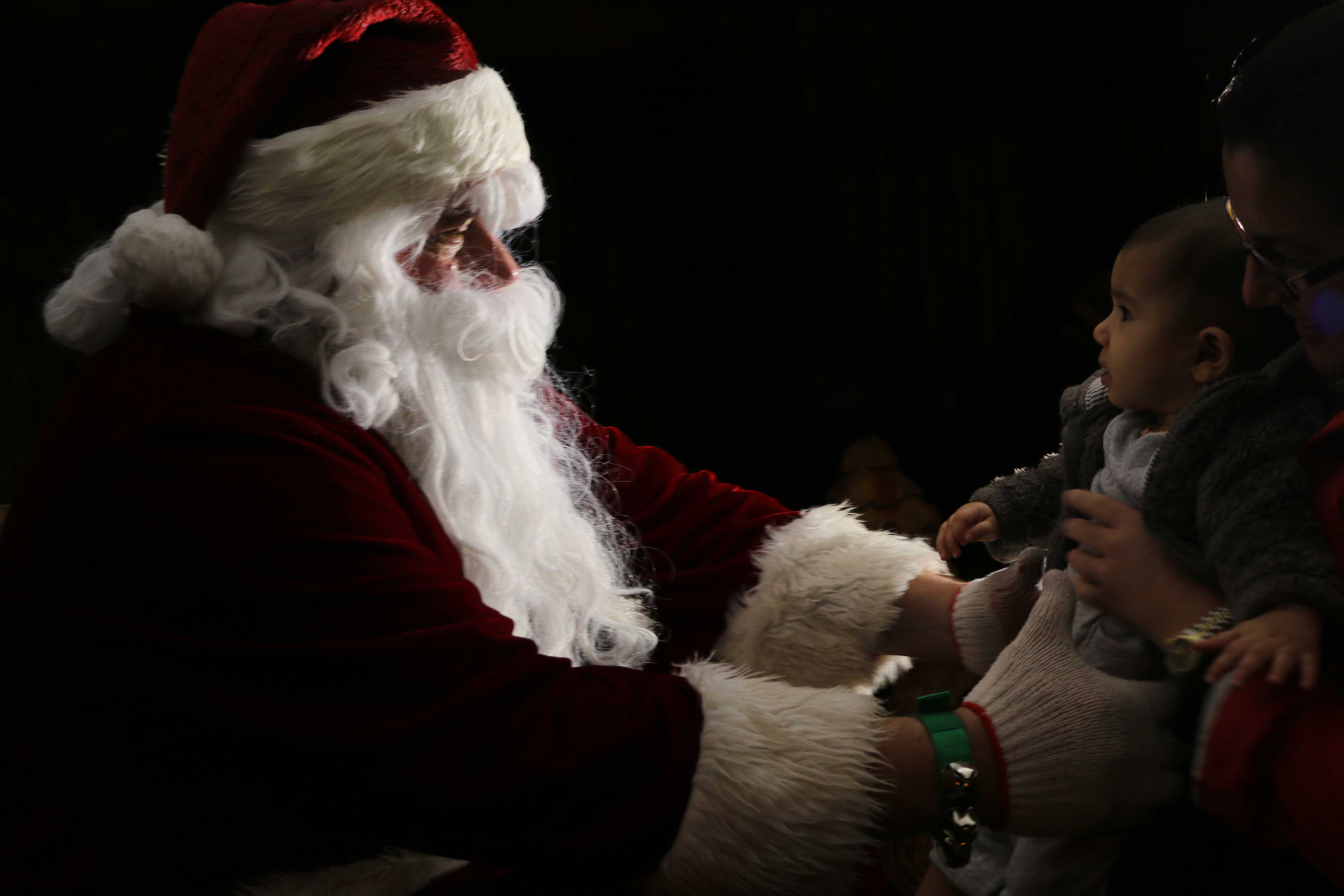 Santa eagerly reaches to embrace six-month-old Morgan Chabra. (Phoebe Barghouty/Peninsula Press)