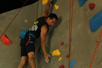 Andrew De Torres climbs a new route on the climbing wall at the Arrillaga Outdoor Education and Recreation Center.