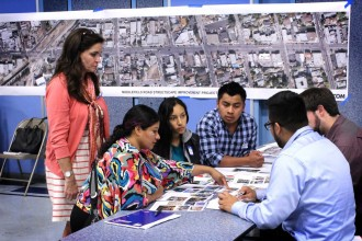 Community members and consultant Millette Litzinger, left, discuss plans for a redesigned Middlefield Road at a design workshop in North Fair Oaks, Calif. on Sept. 30, 2015. As they weighed wider sidewalks against extra parking, many residents were more concerned that a nicer street would spur gentrification. (Jeff Barrera/Peninsula Press)
