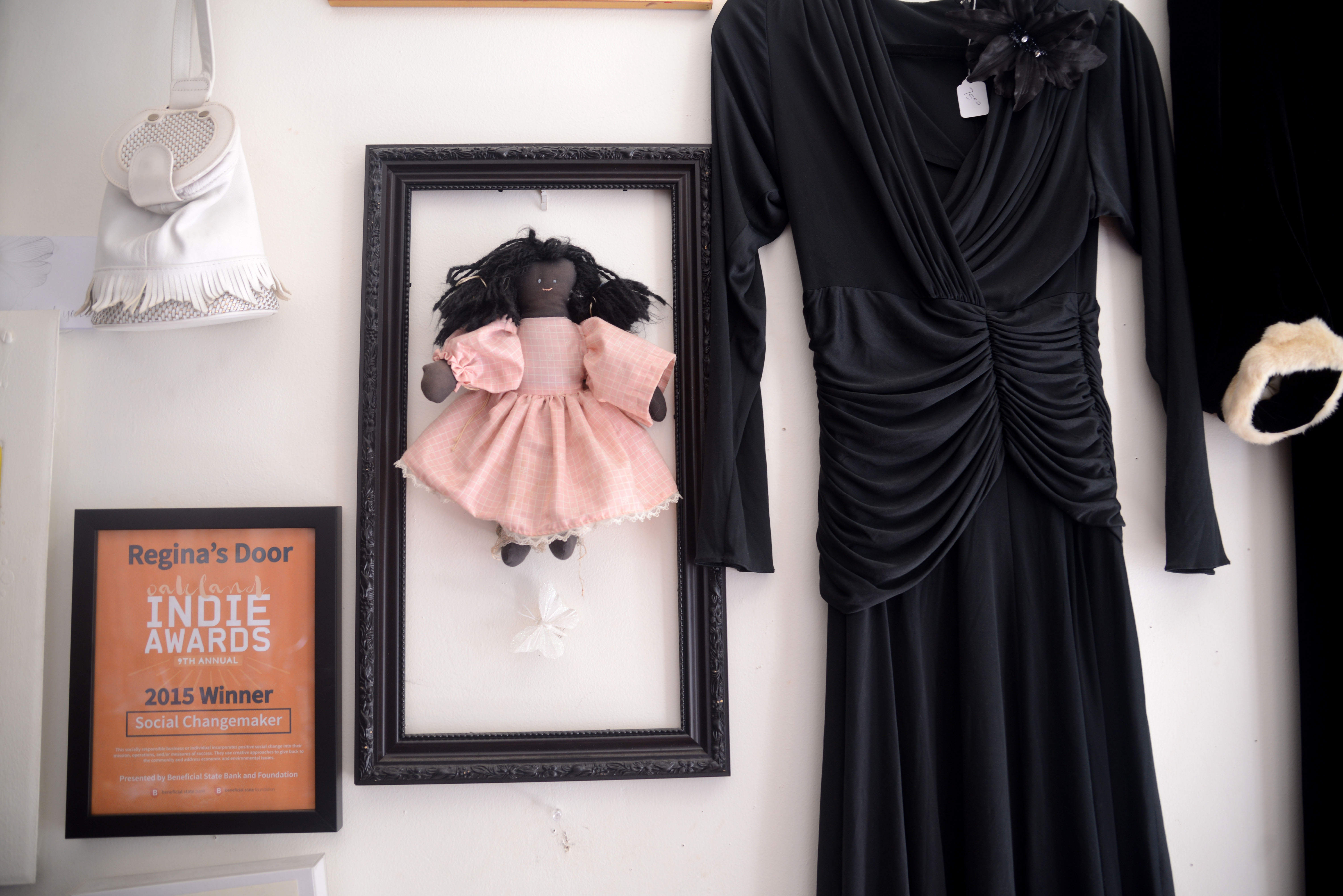 Artwork hangs next to the Social Changemaker Award from the city of Oakland at Regina's Door.
