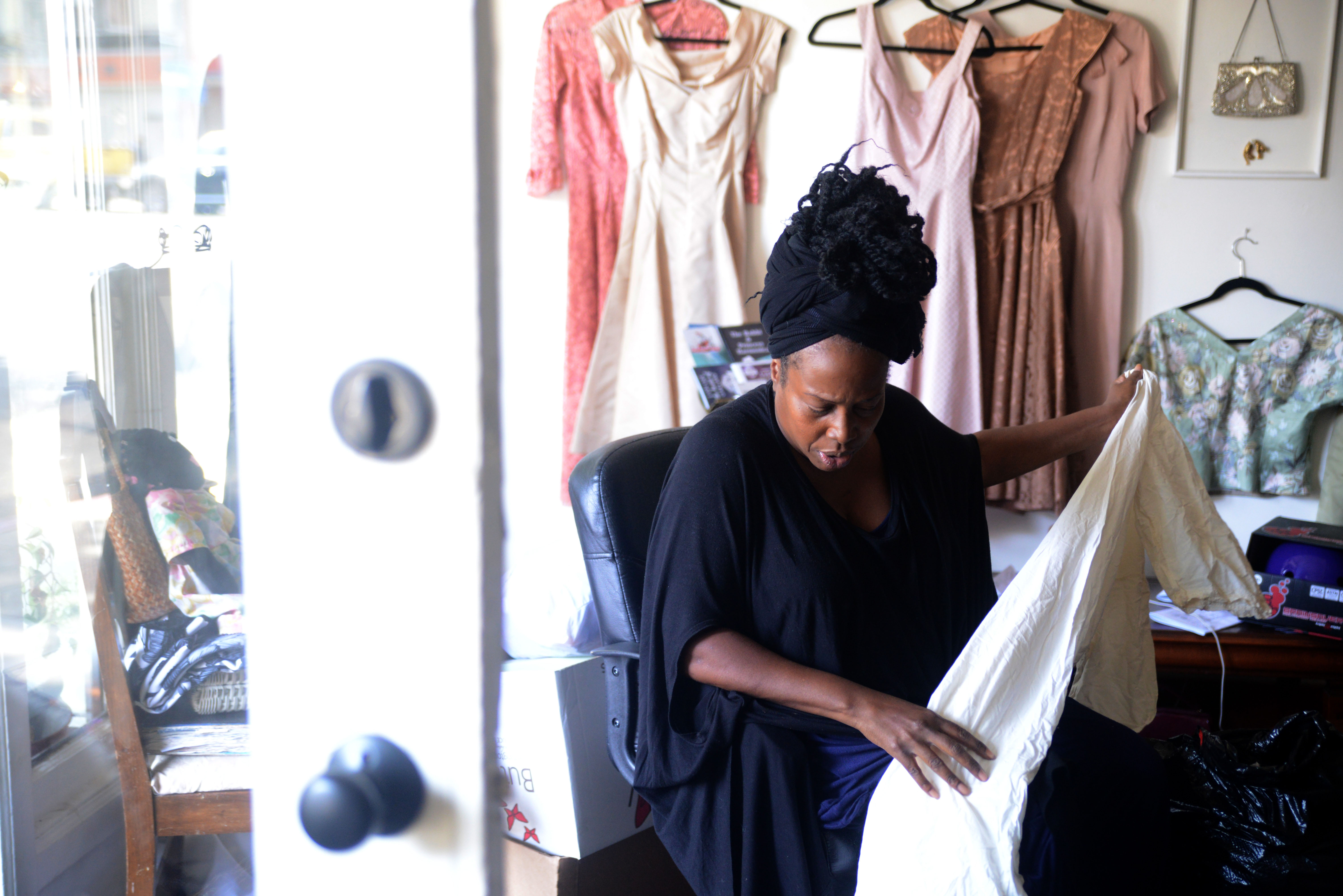 Evans sorts through clothes at her store in downtown Oakland.  (Travis Shafer/Peninsula Press)