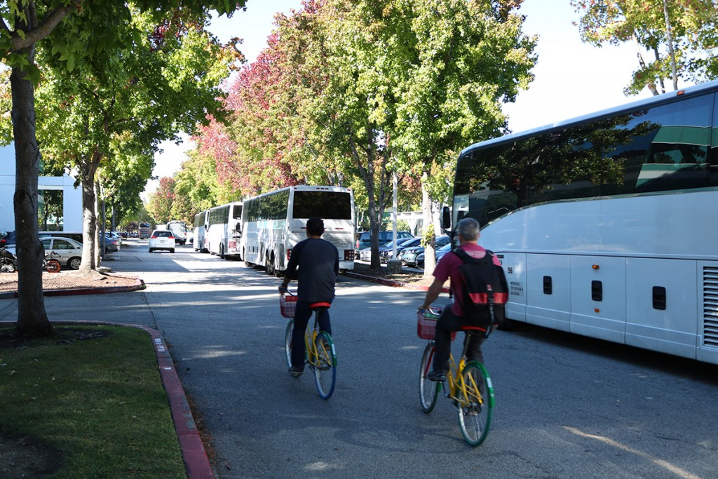 """Two Google employees on """"G-Bikes"""" are passing a line of shuttle busses, Oct. 21, 2016. Both the """"G-Bikes"""" and Google's shuttle buses have helped to bring some traffic relief to Mountain View, the city's Vice Mayor Ken Rosenberg said. (Felix Petermann/Peninsula Press)"""