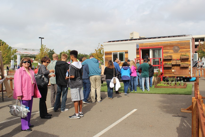 """The mission statement of Fresno State's Tiny House project is: """"Through discovery, diversity and distinction, empower students to design and build an affordable, sustainable and zero-net energy 'Tiny House' solution for the San Joaquin Valley."""" Their 196-square-foot house attracted a long line of interested attendees. (Siqi Lin/Peninsula Press)"""