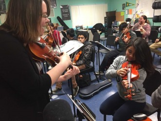 Orchestra teacher Sarah Azevedo leads a group of eighth-graders through scales practice. Orchestra is a new class at Cesar Chavez Academy, made possible by California's new school financing model. (Ashley Gross/Peninsula Press)