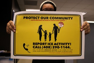 """A rapid responder trainee holds a yellow poster with the words """"PROTECT OUR COMMUNITY, REPORT ICE ACTIVITY! CALL (408) 290-1144"""" and an image of a family walking."""
