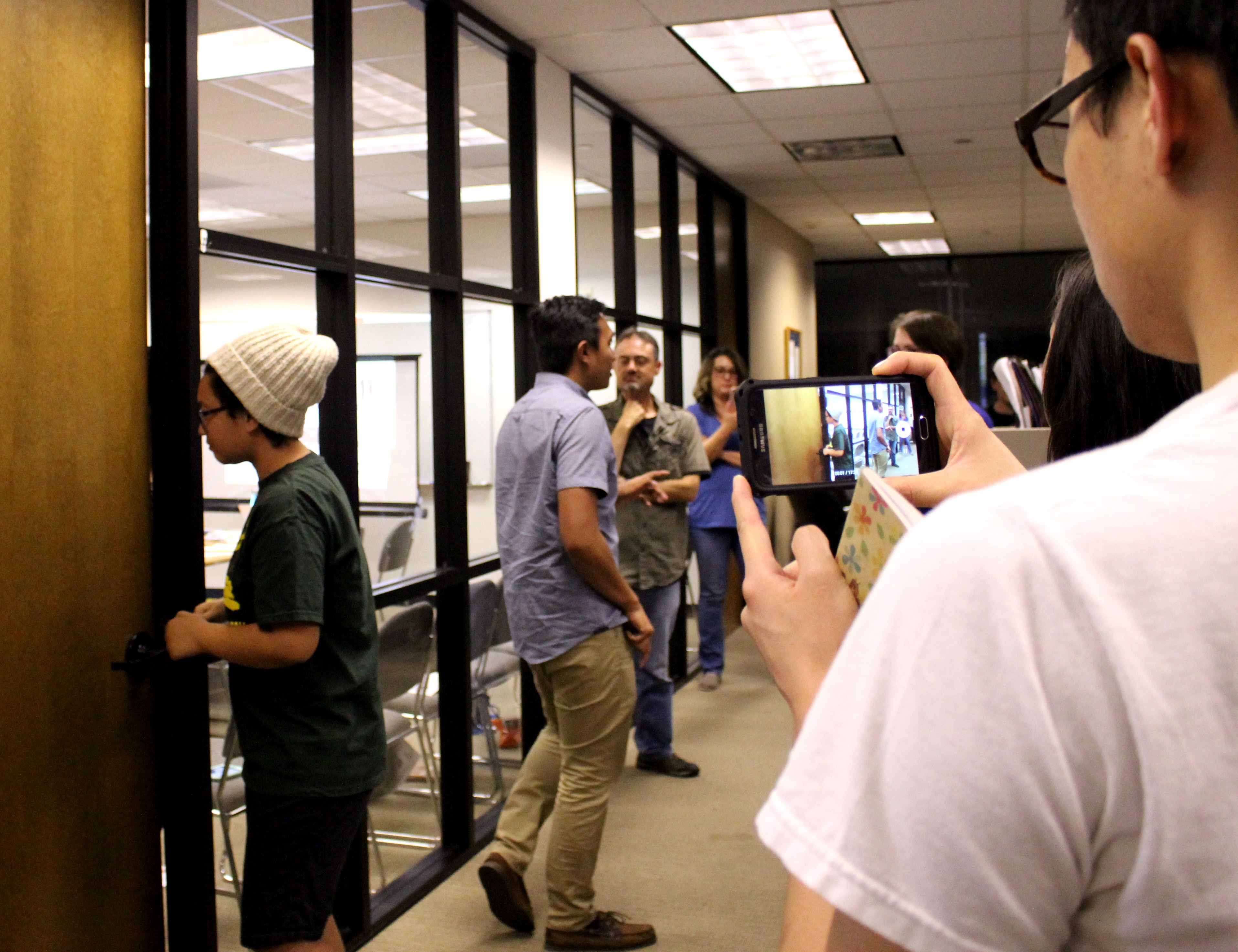 Participants at a Santa Clara Rapid Response Network training use cell phone cameras and notepads to document a simulated ICE enforcement operation. (Jackie Botts/Peninsula Press)
