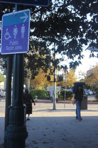 """A man walks behind a """"Public Restrooms"""" sign pointing to one of the three public restrooms in downtown Santa Cruz. (Mark Lieber/Peninsula Press)"""