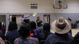 A crowd watches a man and a sign language interpreter in a high school gymnasium.