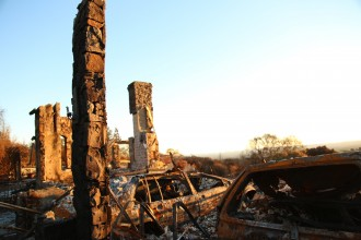 Skeletons of cars and fireplaces emerge amid fire rubble in the upscale neighborhood of Fountaingrove at sunset.