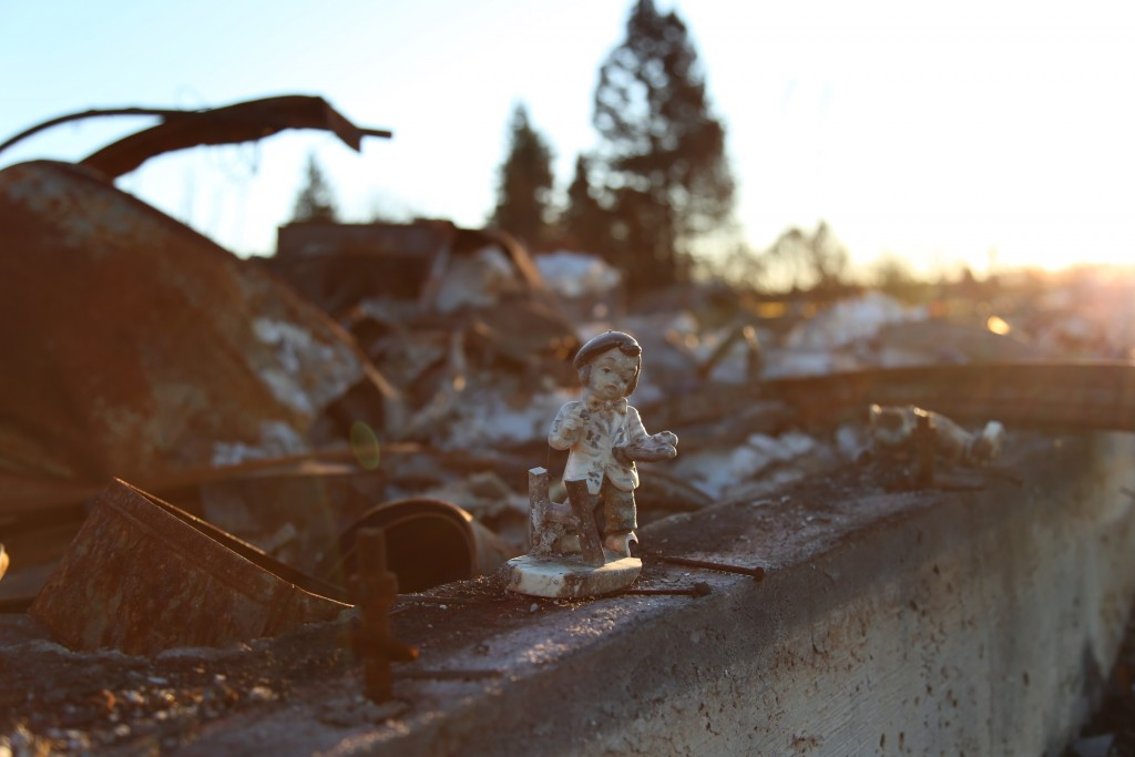 A small figurine of a child is surrounded by rubble in a neighborhood that was burnt to the ground.