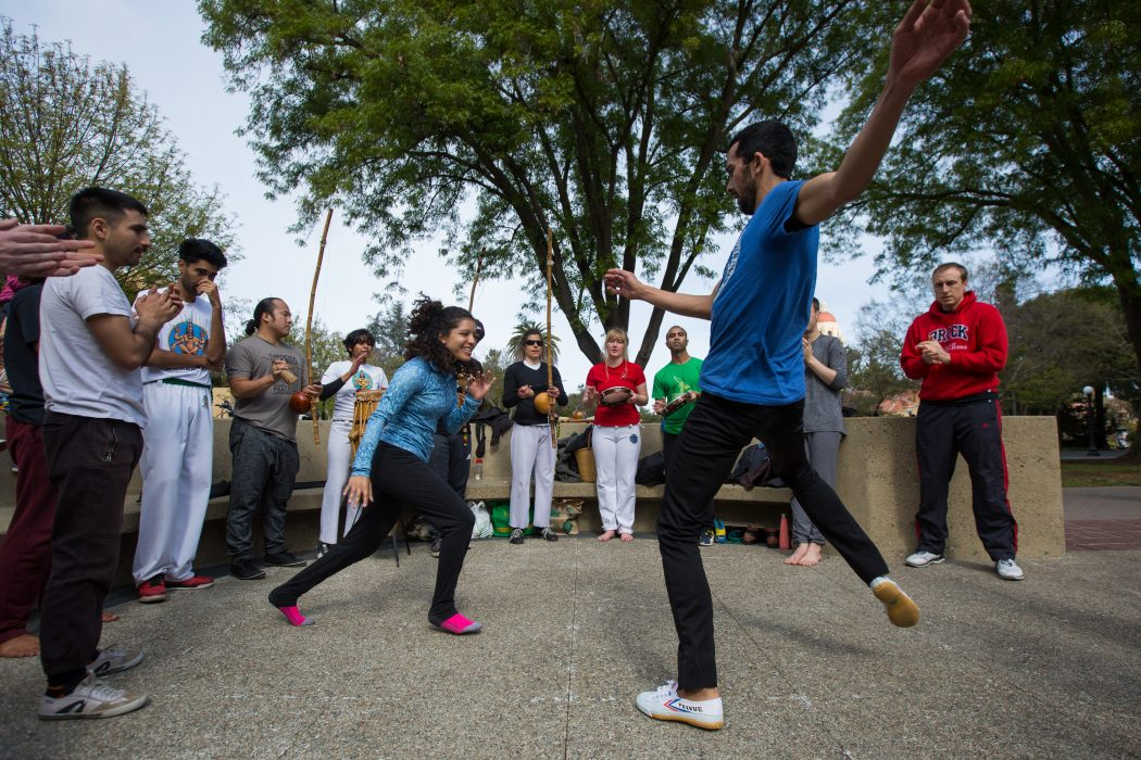 Two players circle around each other at a capoeira event at Stanford University, while onlookers sing and clap.