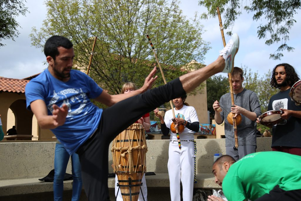 A capoeirista throws a high kick at his ducking opponent, while musicians play behind them.