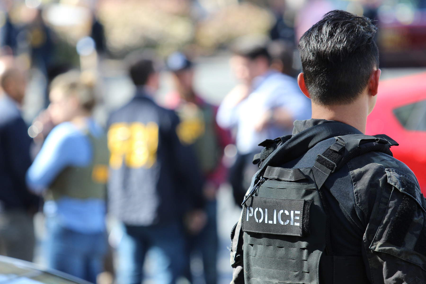 A police officer looks out at fellow officers gathered after a shooting in San Bruno on Tuesday, April 3, 2018.(Anthony Miller/Peninsula Press)