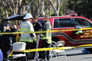"""Inside a police perimeter, fire officials gather near a car that says """"San Bruno Fire Department."""""""