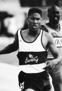 A monochrome photo of Michael Granville racing with his high school jersey on. He has a determined look on his face.