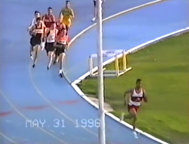 A runner in a white and red jersey leads the pack around the turn on a blue track.