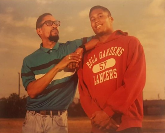 Michael Granville in a red sweater poses with his father who rests an elbow on his shoulder.