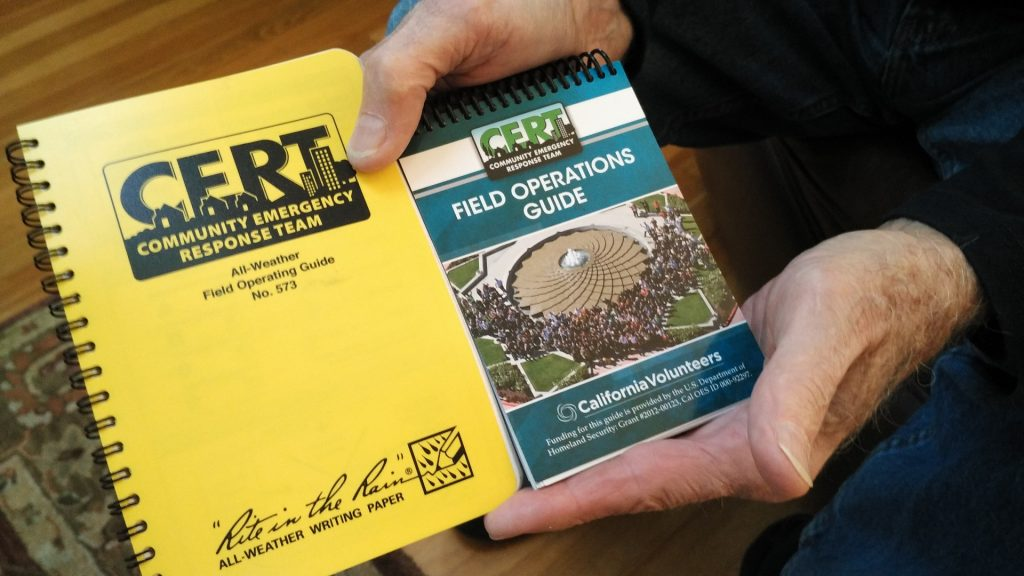Dan Melick shows the field guides he uses as a CERT and an ESV in Palo Alto. (Amy Cruz/Peninsula Press)