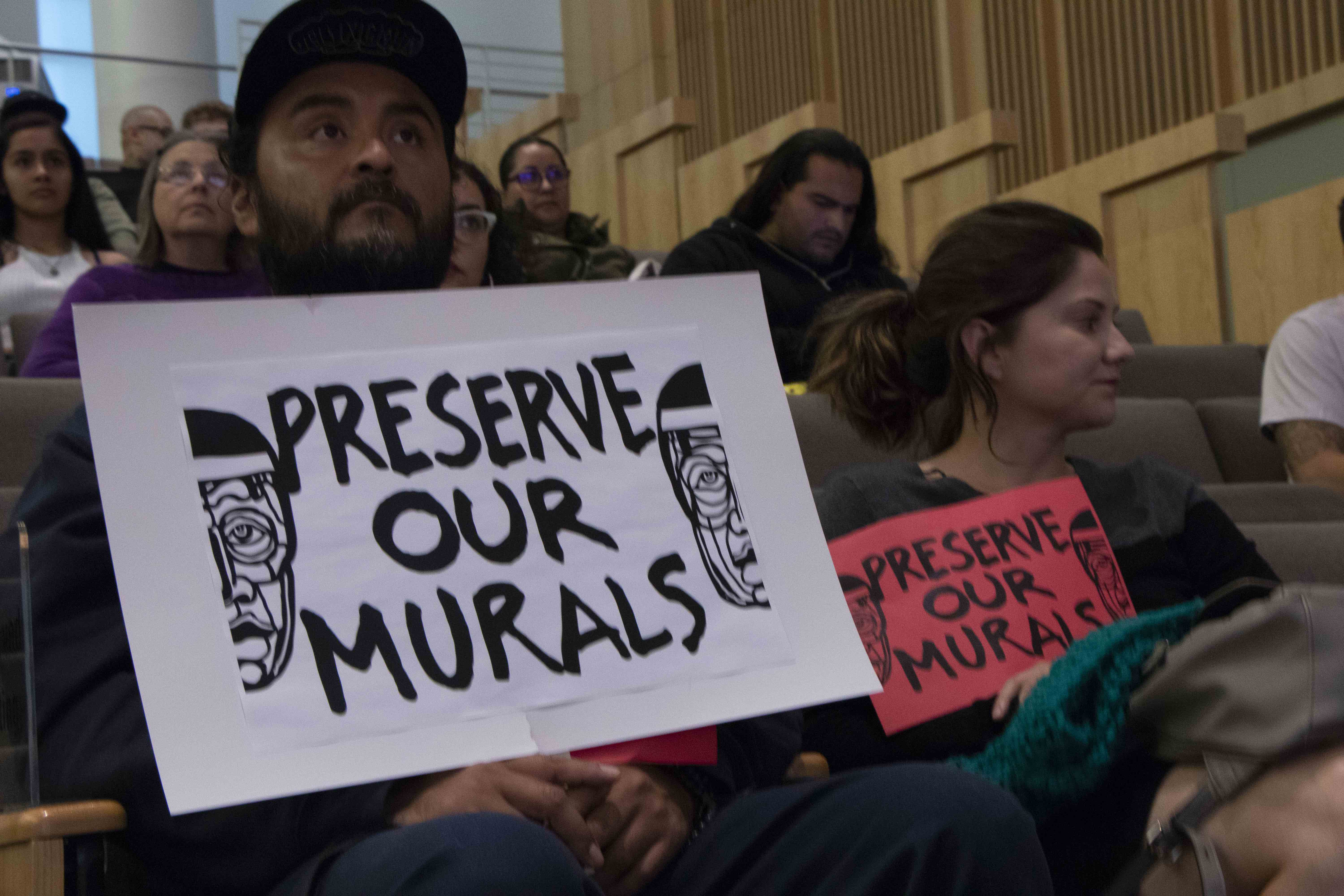 Residents Juan Carlos Araujo and Maricela Lechuga hold up signs urging the Historic Landmarks Commission to help protect Chicano murals at City Hall in San Jose, Calif., on Wednesday, Oct. 2, 2019. (Vanessa Ochavillo/Peninsula Press)