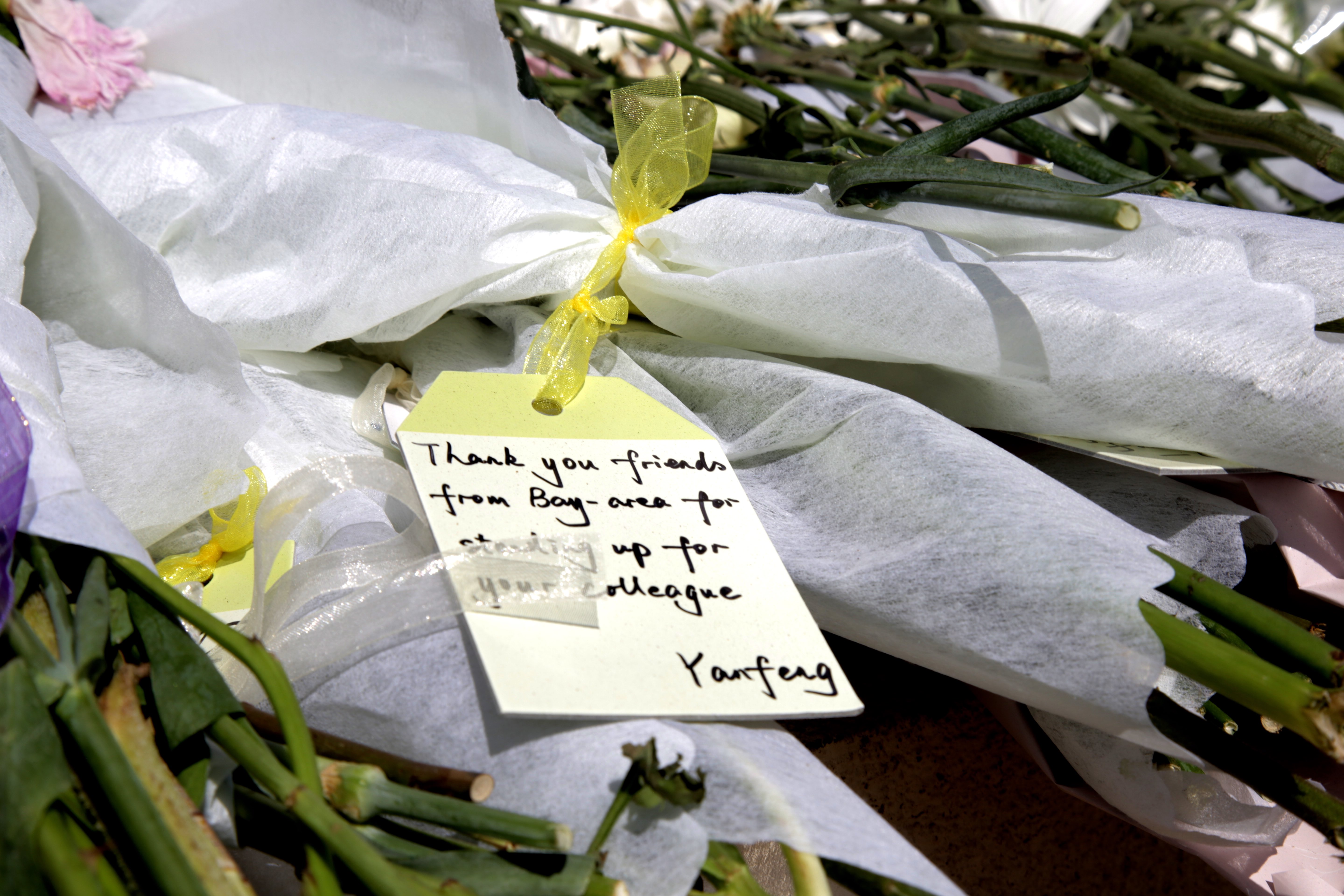 """Flowers are brought to the scene on Thursday September 26, 2019 by protestors who express their condolences and honor the passing of Qin Chen. One of the cards, written by a protestor named Yanfeng, says, """"Thank you friends from Bay Area for standing up for your colleague.""""  (Qian Chen/Peninsula Press)"""