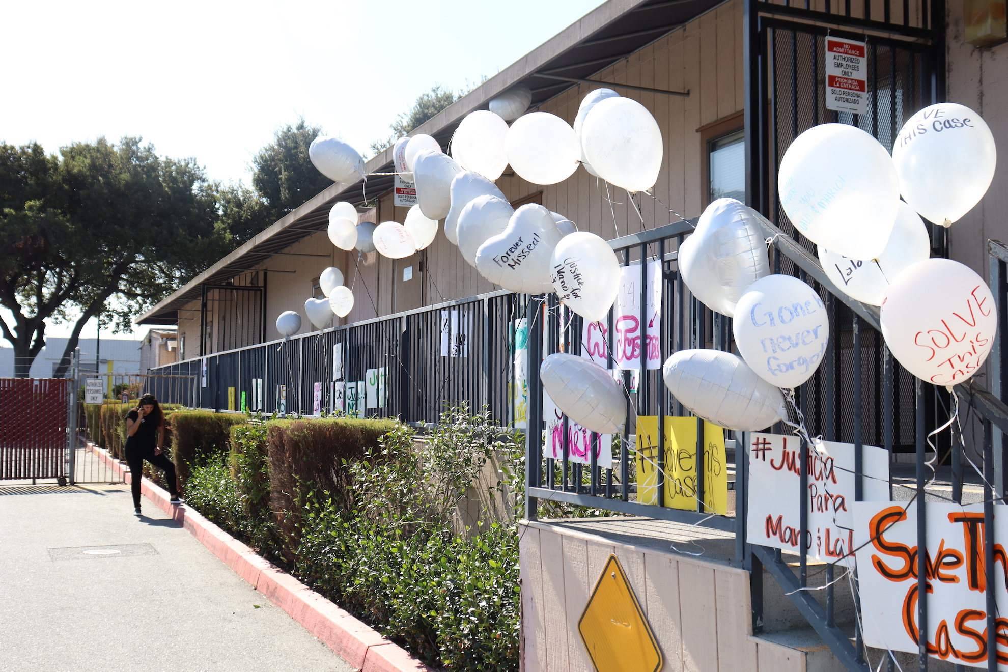 Balloons and signs line the railing at the East Palo Alto Police Department following the march for justice on Sunday, Oct. 13, 2019. (Astrid Casimire/Peninsula Press)