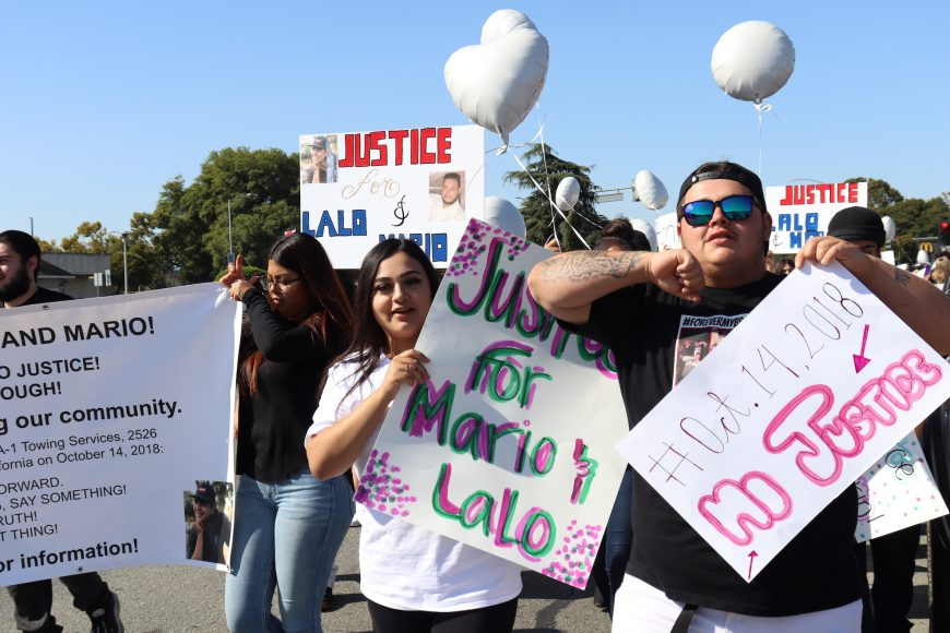 """Supporters hold signs demanding justice for Eduardo """"Lalo"""" Sandoval and Mario Mendez during the march on Bay Road, East Palo Alto, Calif., Sunday, Oct. 13, 2019. (Astrid Casimire/Peninsula Press)"""