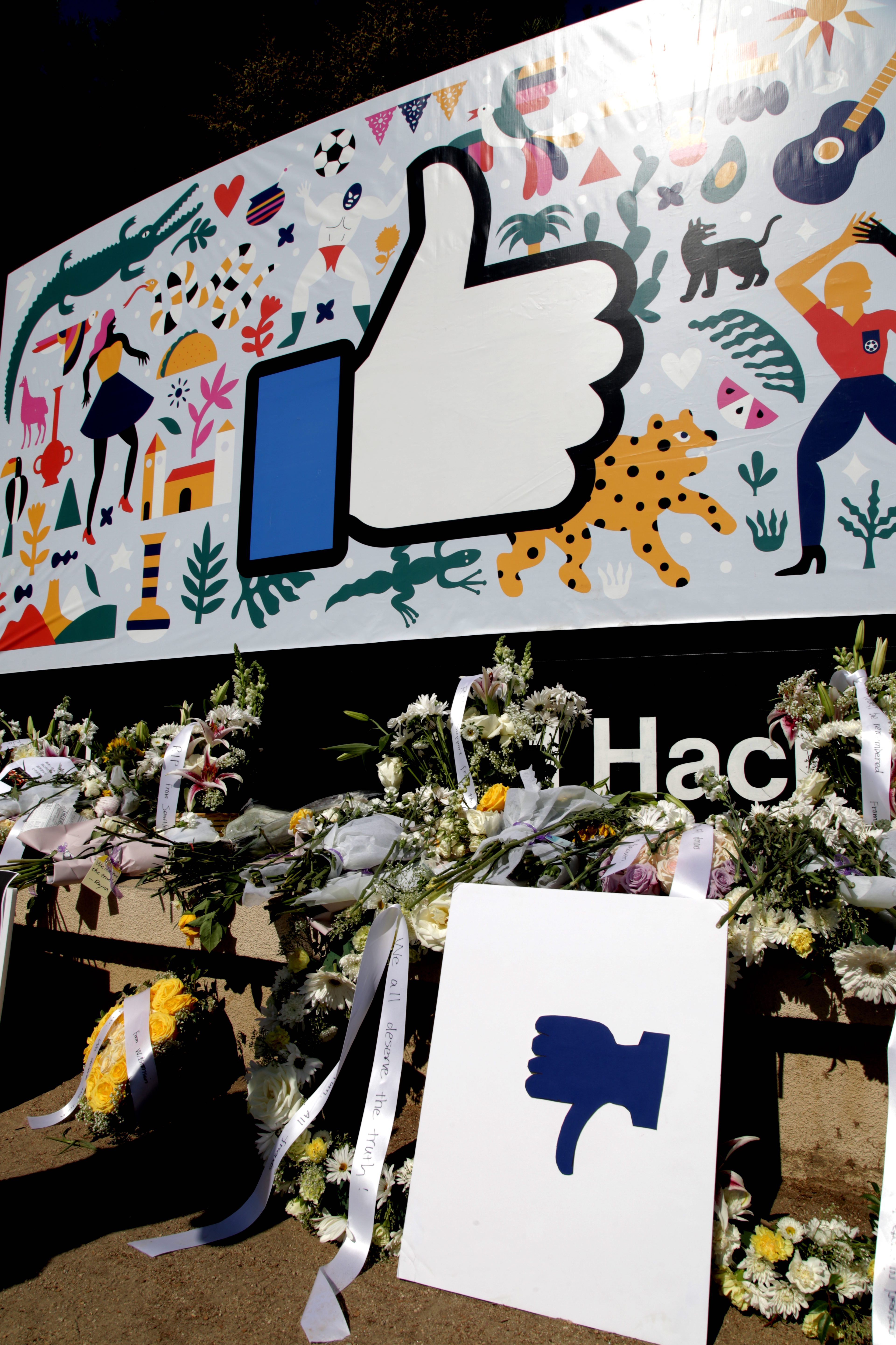 """After the protest, a thumbs-down sign, along with memorial flowers, was left in front of Facebook's iconic thumbs-up """"like"""" sign at the entrance of the company's Menlo Park campus on Thursday September 26, 2019. Protestors say they are not happy with the company's silence towards Qin Chen's suicide case."""