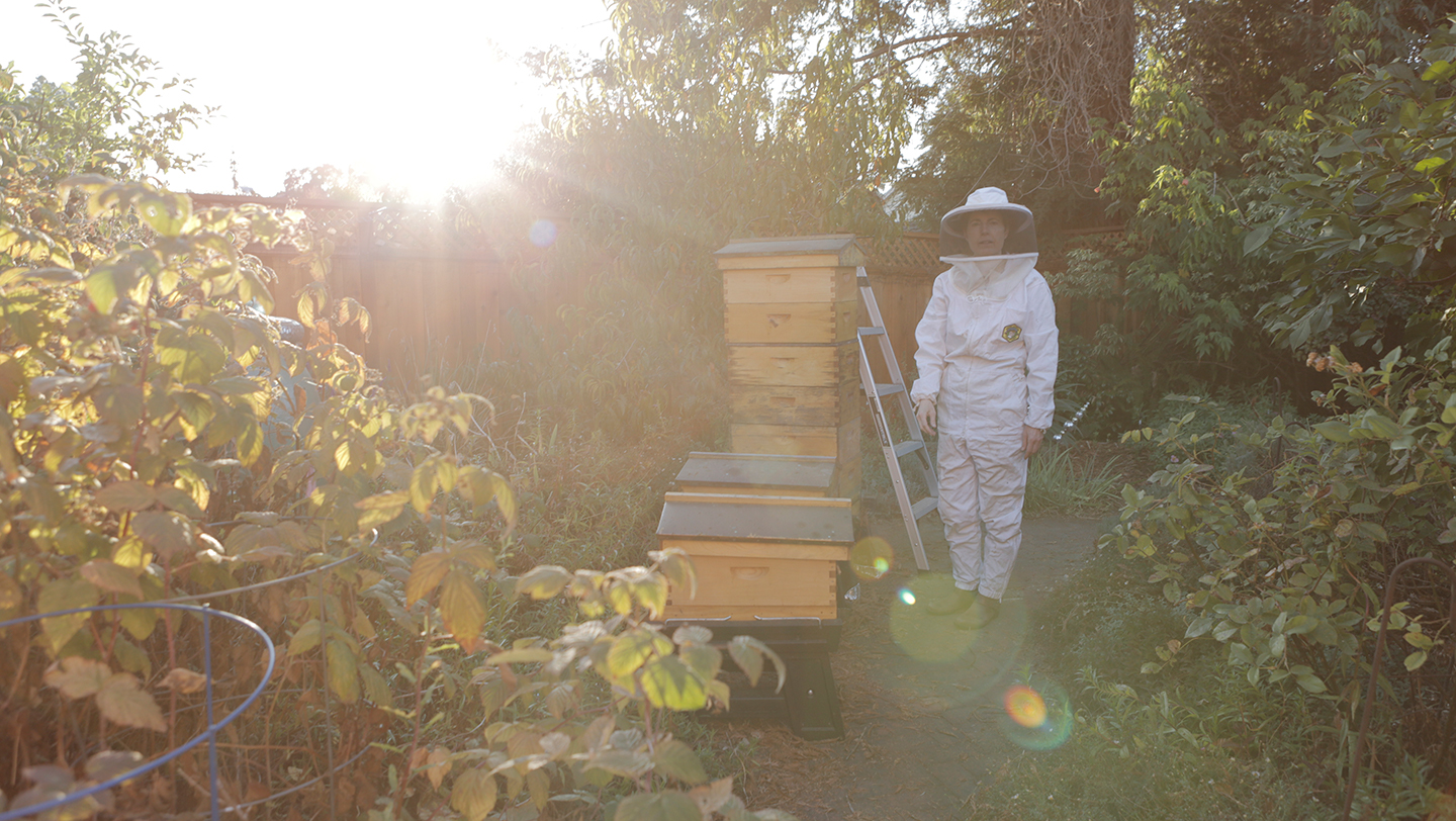 Beekeeper Tori Muir wears a protective suit while standing in her backyard next to her honeybee colony on on Sunday, Oct. 13, 2019 in Burlingame, Calif. (Salma Loum/ Peninsula Press)