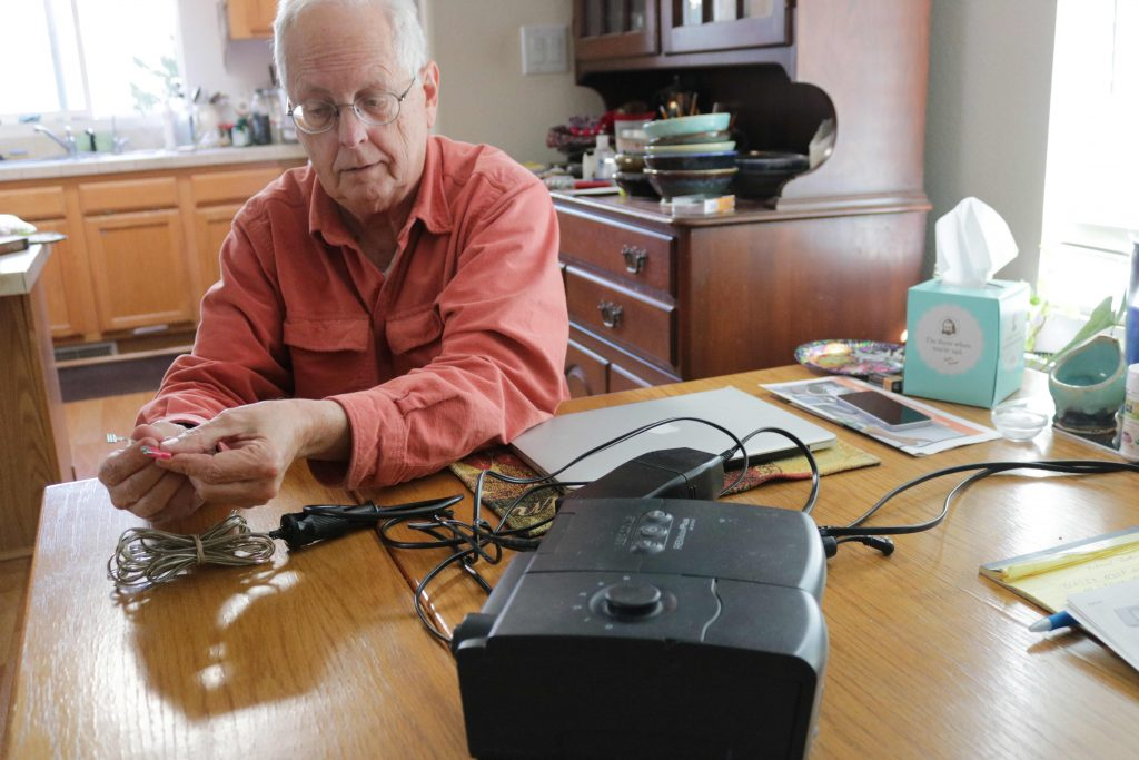 Tom Devine attaches a backup battery to his CPAP device