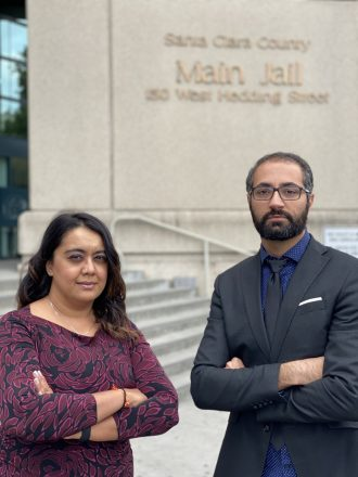 Charlene Mahabali and Alen Yaghoubi stand in front of the stairs and a sign for the Santa Clara County Main Jail at 150 West Hedding Street in San Jose