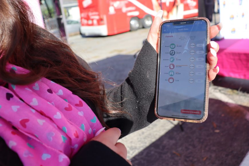 Yuri Fong, health educator with Life Saving Images Inc, demonstrates how to use their app to connect to health screenings for major cancers, heart disease and diabetes. (Astrid Casimire/Peninsula Press)