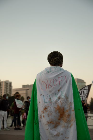 """A protestor wears the Nigerian flag with """"Okofi Lekki"""" written on it in Oakland, Calif., Saturday, Oct. 24, 2020. The massacre on Tuesday, Oct. 20, took place in Lagos at the Lekki toll gate. (Noah Cortez, Peninsula Press)"""