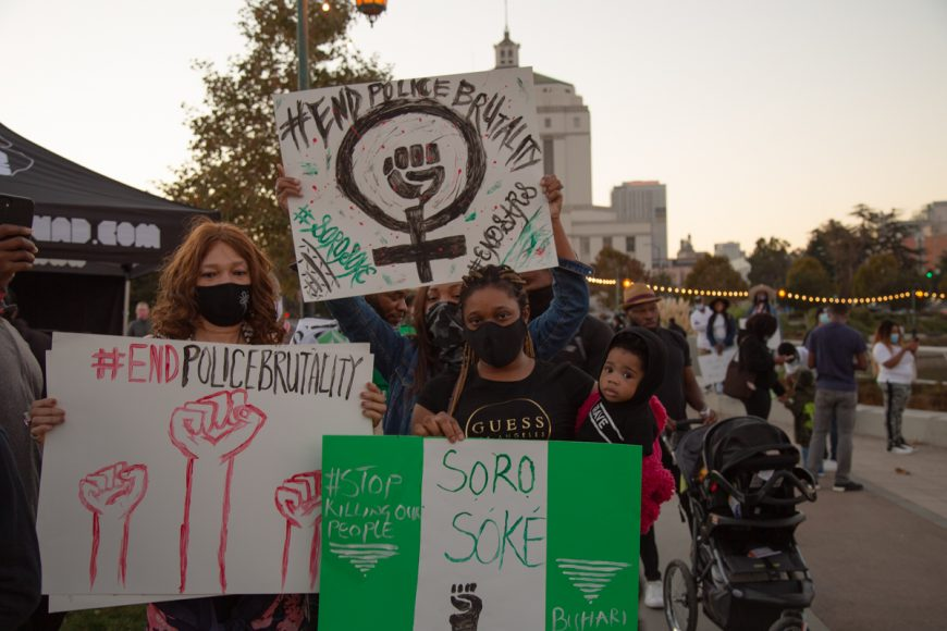 Women hold up signs at the #endSARS protest in Oakland, Calif., Saturday, Oct. 24, 2020. The theme of police brutality in Nigeria parallels a similar issue in the United States. (Noah Cortez, Peninsula Press)