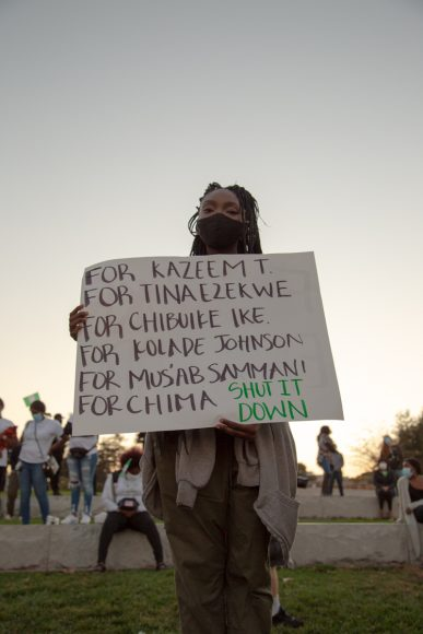 Onyinyechi Nwosu holds up a sign in Oakland, Calif. Saturday, Oct. 24, 2020, honoring those killed by Nigerian armed forces in Lagos, Nigeria, on Tuesday, Oct. 20, 2020. (Noah Cortez, Peninsula Press)