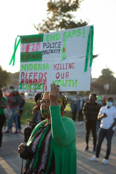 A woman holds up a sign in Oakland, Calif., Satuday, Oct. 24, 2020, calling for an end to police brutality in Nigeria.(Noah Cortez, Peninsula Press)