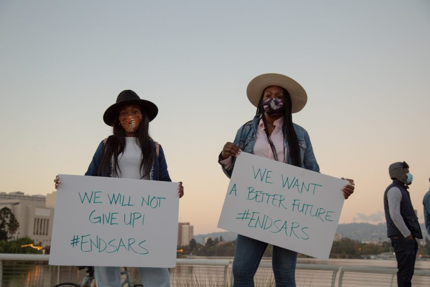 Bolaji Idakoji (left) and Olayinka Sanni (right) hold up signs during the #endSARS protest in Oakland, Calif., Satuday, Oct. 24, 2020. (Noah Cortez, Peninsula Press)