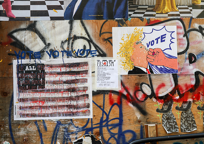 """Street art in SoHo exhorts the public to acknowledge the """"early warning signs of fascism."""" (Iman Floyd-Carroll/Peninsula Press)"""