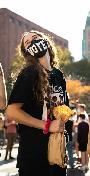 """A young woman proudly sports a """"vote"""" mask, standing out amongst the crowd at Washington Square Park. The 2020 election was marked by historical voter turnout in the U.S. with nearly 150 million people casting ballots - the highest voter turnout for a presidential election in over a century. (Iman Floyd-Carroll/Peninsula Press)"""