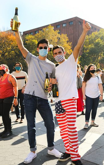 NYC residents Blair Horner and Brett Allen, who dons patriotic pants, raise champagne and a triumphant 'thumbs-up' amidst the festivities at Washington Square Park. (Iman Floyd-Carroll/Peninsula Press)