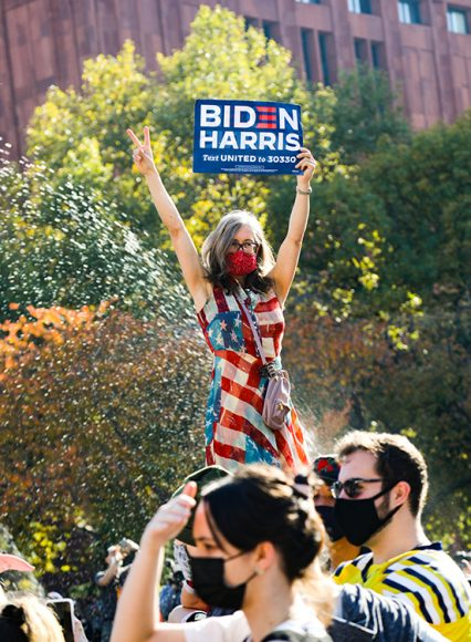 """Standing atop a fountain, a masked woman in a festive American-flag print dress raises a Biden-Harris sign and flashes a peace sign to the onlooking crowd. Prior to the announcement, President-Elect Joseph R. Biden Jr. tweeted """"A nation united. A nation strengthened. A nation healed. The United States of America."""" (Iman Floyd-Carroll/Peninsula Press)"""