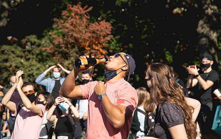 Celebrating amidst the thousands of NYC residents who flooded the street after Biden's win, a man pulls down his mask to sip from a bottle of champagne in Washington Square Park on Nov. 8. (Iman Floyd-Carroll/Peninsula Press)