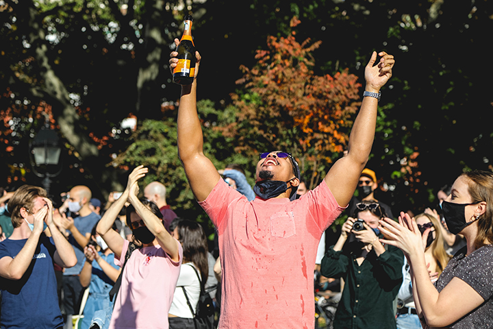 Wielding a bottle of champagne, a man throws his hands up triumphantly displaying joy and relief – two common emotions that reverberated throughout New York City, a liberal hub and President Trump's hometown, the morning of  Nov 8. (Iman Floyd-Carroll/Peninsula Press)