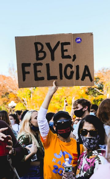 """A woman with a """"New York"""" mask defiantly holds up a cardboard sign painted """"Bye, Felecia."""" The phrase """"Bye, Felicia"""" came from a scene in the American comedy film 'Friday' famously starring the rapper/actor Ice Cube. Per the movie reference, the phrase is used colloquially as a dismissive send-off. (Iman Floyd-Carroll/Peninsula Press)"""