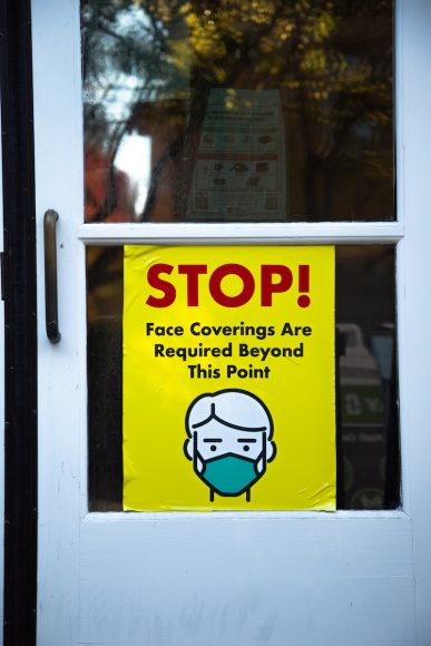 A poster on the door of Casper dining hall reminds students and faculty to wear a face covering before entering the building. As of December 6, 2020, indoor and outdoor seating is prohibited. (Noah Cortez, Peninsula Press)